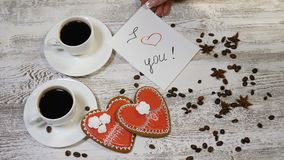 Love relations. St. Valentine concept. Top view of two cups of coffee and two ginger biscuit heart shaped are on wooden. Love relations. St. Valentine concept stock video footage
