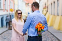 Love and relationship concept - young man giving flowers to his. Love and relationship concept - young men giving flowers to his girlfriend in the city Royalty Free Stock Images