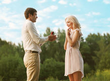 Love, relationship, couple, wedding, romantic. Men proposing to a women in the park Royalty Free Stock Photography