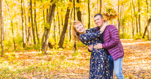 Love, relationship, family and people concept - smiling couple having fun in autumn park. Royalty Free Stock Images