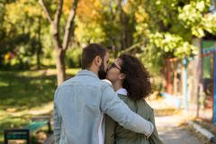 Love, relationship, family and people concept - smiling couple kissing in autumn park stock photography