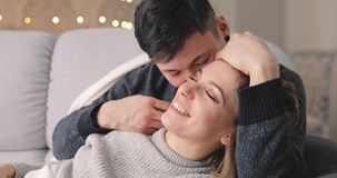 Love, happiness of young couple hug on sofa in home. Love, relationship, happiness of young couple hug on a cozy sofa in home room, he kiss her stock footage