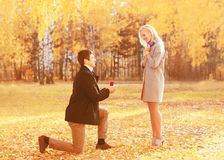 Love, relationships, engagement and wedding concept - kneeled man proposes a woman to marry, red box ring, happy romantic couple royalty free stock photography