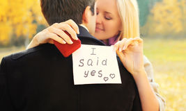 Love, relationships, engagement and wedding concept - man proposes a woman to marry, red box ring, happy young romantic couple. Love, relationships, engagement Stock Photography