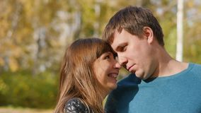 Love, relationships, season and people concept - happy young couple having fun in autumn park.  stock footage