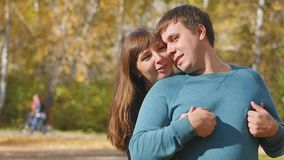 Love, relationships, season and people concept - happy young couple having fun in autumn park stock video footage