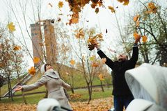 Love, relationships, season and people concept - happy young couple throwing autumn leaves up in park. stock photography