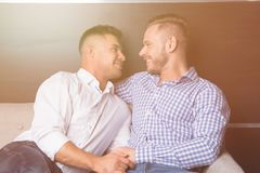 Love and relationships. Two happy guys together on couch stock image