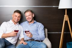 Love and relationships. Two married guys together on couch stock photo