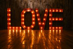 LOVE retro letters glowing with light bulbs. LOVE volume retro letters glowing with light bulbs on a wooden background Royalty Free Stock Image