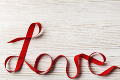 Love Ribbon Twisted Word, Wooden Background. Valentine Day Concept Stock Photo