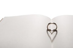 Love ring. The shadow of ring is heart on a book royalty free stock photos