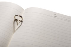 Love ring. The shadow of ring is heart on a book stock image