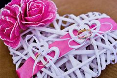 Love rings of the newlyweds on heart decorated with pink bow stock images