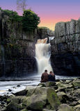 Love On The Rocks. Romantic Couple sitting on rocks watch the Sun go down at High Force Waterfall in Co Durham reputed to be the highest unbroken fall of water stock photo