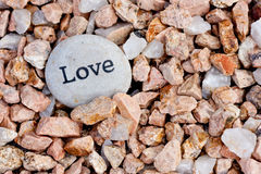 Love on the rocks. Close up of 'love' stone on textured rock background Stock Images
