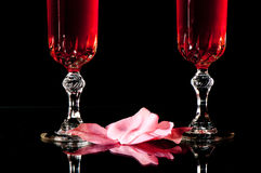 Love and romance. Pink rose petals and crystal champagne glasses reflected on a black background Stock Images