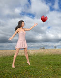 Love, Romance, Hope, Beauty, Woman. A beautiful young woman sees love, romance, peace, and hope in a heart shaped red balloon as it flies across a green field Stock Photos