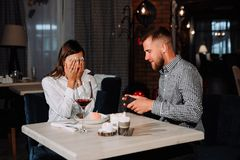Portrait of happy and surprised young woman receiving present from boyfriend while sitting in cafe. Love, romance, valentines day, couple and people concept Stock Image
