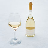 Love, romance, winter holidays, New Year celebration concept. Bottle and glass of white wine chilled by snow. Royalty Free Stock Photography
