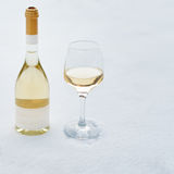 Love, romance, winter holidays, New Year celebration concept. Bottle and glass of white wine chilled by snow. Royalty Free Stock Photo