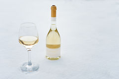 Love, romance, winter holidays, New Year celebration concept. Bottle and glass of white wine chilled by snow. Stock Photos