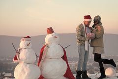 Love and romance, xmas. Santa muscular men and girl with snowman. New year boyfriend and girlfriend outdoor. Christmas couple in love of men and woman. Snowman stock photo