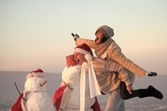 Love and romance, xmas. Snowman, winter holiday celebration. Santa muscular men and girl with snowman. New year boyfriend and girlfriend outdoor. Christmas royalty free stock photo