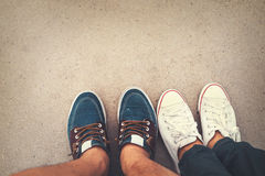 Love romantic couple - top view sneakers on the ground of man and woman feet in outdoor lifestyle Stock Photos