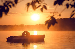 Love and romantic golden river sunset. Silhouette of couple on boat backlit by sunlight. Love and colors of romantic golden river sunset with fog and silhouette Royalty Free Stock Images