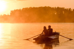 Love and romantic golden river sunset. Silhouette of couple on boat backlit by sunlight. Love and colors of romantic golden river sunset with fog and silhouette Stock Image