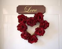 Love and roses. Love in the shape of a heart of roses on a door stock photo