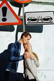 Love without rules a warning. traffic sign on the sidelines and a loving couple under him, hugging and kissing. without stock photos