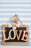 LOVE on rustic chalkboard on stripes Royalty Free Stock Photography
