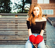 Love, sadness and loneliness. Beautiful long-haired girl in sad loneliness summer evening. She is holding a big red Royalty Free Stock Photo
