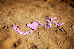 Love on the sand. Inscription love on the sand of confetti Stock Image