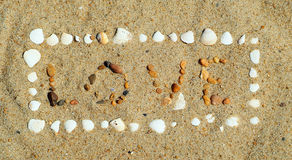 Love sand. Love written in sand with rocks and shells royalty free stock photo