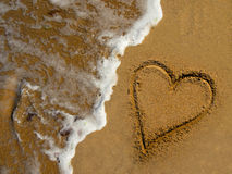 Love Sand Sea. Love written on sand and erased by the sea wave Stock Photos