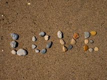 Love Sand. Love written with little rocks on the wet sand Royalty Free Stock Images