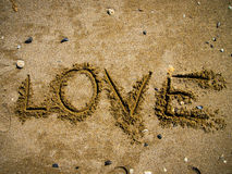 Love Sand. Love written on the wet sand Stock Images