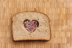 Love Sandwich. Peanut butter and jelly sandwich with a heart cut out and cute little sprinkles on a bamboo cutting board Royalty Free Stock Photo