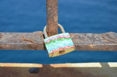 Love sea lock. A lock locked on a rusty metal bar. The lock has hand painted with pink, white, green and blue some surreal waves. It symbolizes eternal love stock image