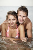 Love in the sea. Young couple relaxing at beach in Italian resort Caorle bathing in sea water and summer sun royalty free stock photos