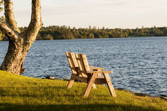 Love seat at lake in fall. Wooden love seat for two on the shore of a lake on autumn afternoon.  Moosehead Lake, Greenville, Maine Stock Image