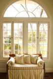Love seat in window. A love seat lit by the morning sun in the window royalty free stock photo