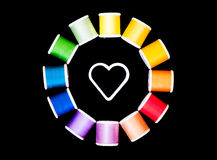 Love sewing - circle of threads around a white heart shape center. Color wheel circle of sewing threads around a white heart shape - isolated on black Stock Image