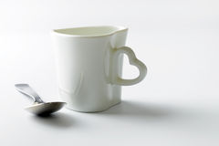 Love shape cup with tea spoon Royalty Free Stock Image