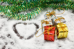 Love shape, gifts box, tree on snow background. Royalty Free Stock Image