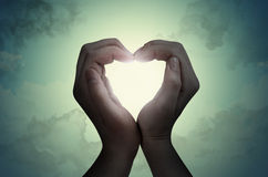 Love shape hand silhouette. In sky Royalty Free Stock Image