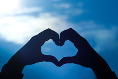 Love shape hand silhouette. In blue sky Stock Photography